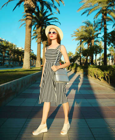 Attractive woman wearing a striped dress and summer straw hat outdoors over palm trees background Stok Fotoğraf - 152443780