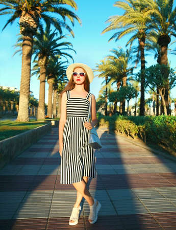 Attractive woman wearing a striped dress and summer straw hat outdoors over palm trees background Stok Fotoğraf - 152443533
