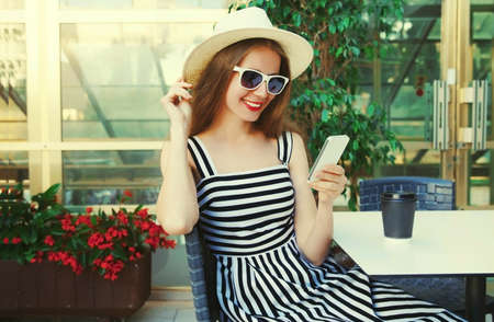 Beautiful young woman sitting at a table in a cafe with phone Stok Fotoğraf - 152665887