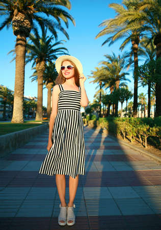 Attractive woman wearing a striped dress and summer straw hat outdoors over palm trees background Stok Fotoğraf - 152443794