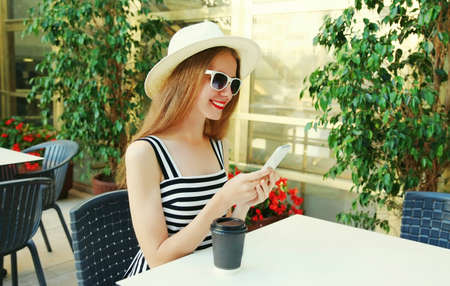 Beautiful young woman sitting at a table in a cafe with phone Stok Fotoğraf