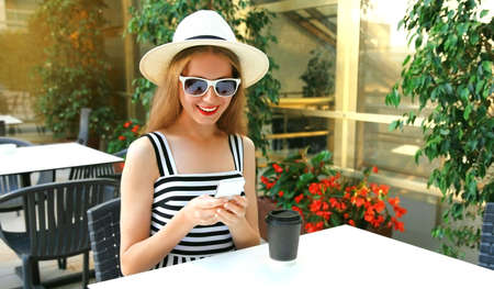 Beautiful young woman sitting at a table in a cafe with phone Stok Fotoğraf - 152665890