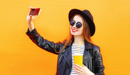 Happy smiling young woman taking selfie picture by phone with cup of juice over orange wall background Stok Fotoğraf - 152665892