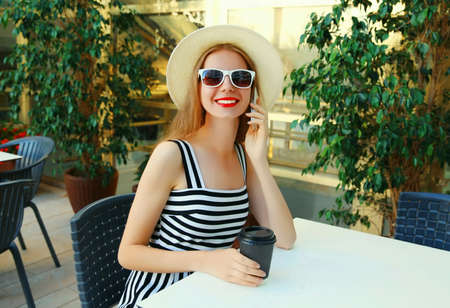 Beautiful young woman calling on smartphone sitting at a table in a cafe with coffee cup Stok Fotoğraf - 152443359
