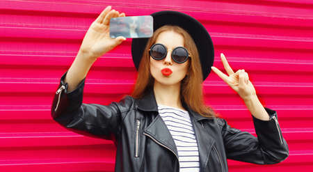 Attractive young woman taking selfie picture by phone blowing red lips sending sweet air kiss over colorful pink background Banque d'images