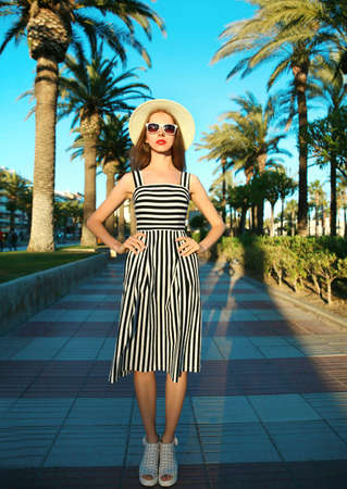 Attractive woman wearing a striped dress and summer straw hat outdoors over palm trees background Stok Fotoğraf - 152443932