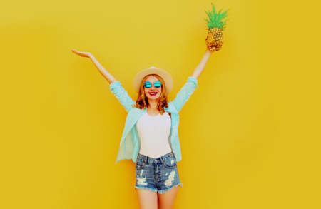 Summer image happy woman raising her hands up with pineapple having fun wearing a straw hat, shorts over colorful yellow background Stok Fotoğraf - 152500006