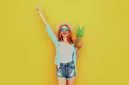 Summer image happy woman raising her hands up with pineapple having fun wearing a straw hat, shorts over colorful yellow background Stok Fotoğraf - 152500235