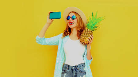 Summer portrait of happy smiling woman with pineapple taking selfie picture by smartphone wearing a straw hat, sunglasses over colorful yellow background Stok Fotoğraf - 152500013