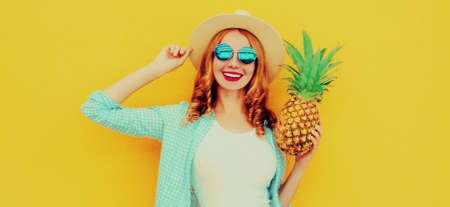 Summer portrait happy smiling woman with pineapple having fun wearing a straw hat, sunglasses over colorful yellow background