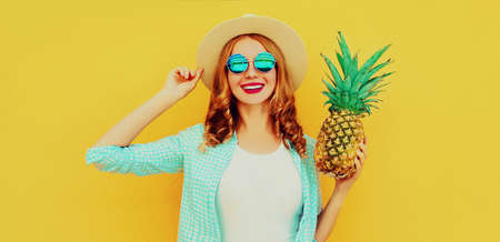 Summer portrait happy smiling woman with pineapple having fun wearing a straw hat, sunglasses over colorful yellow background Stok Fotoğraf - 152500241