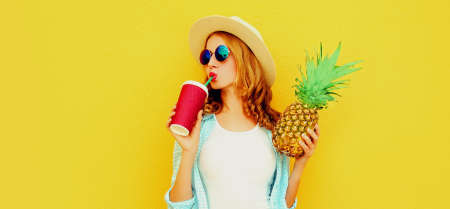 Summer portrait of attractive woman drinking juice holding pineapple wearing a straw hat, sunglasses over colorful yellow background Stok Fotoğraf - 152500044