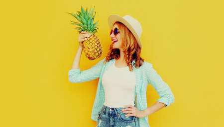 Summer portrait happy smiling woman with pineapple having fun wearing a straw hat, sunglasses over colorful yellow background Stok Fotoğraf - 152500033