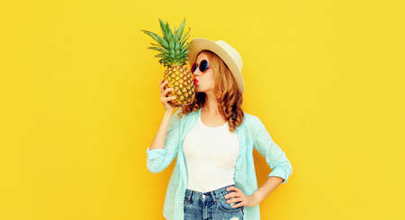 Summer image of attractive woman kissing tropical pineapple wearing a straw hat, sunglasses over colorful yellow background Stok Fotoğraf - 152499768
