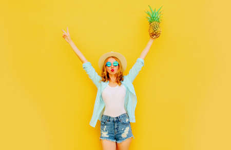 Summer image happy woman raising her hands up with pineapple having fun wearing a straw hat, shorts over colorful yellow background Stok Fotoğraf - 152500309