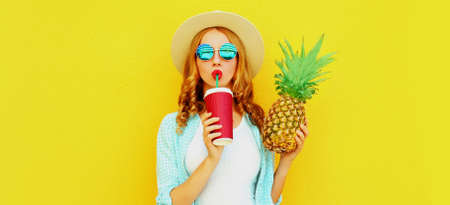 Summer portrait of attractive woman drinking juice holding pineapple wearing a straw hat, sunglasses over colorful yellow background Stok Fotoğraf - 152500252
