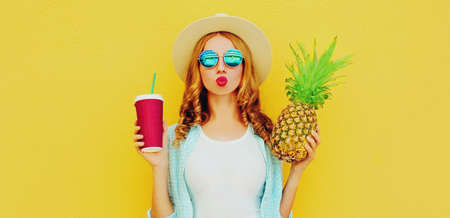 Summer portrait of attractive woman with cup of juice and pineapple blowing red lips sending sweet air kiss wearing a straw hat, sunglasses over colorful yellow background Stok Fotoğraf - 152499735