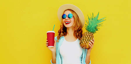 Summer portrait of happy laughing woman with cup of juice and pineapple having fun wearing a straw hat, sunglasses over colorful yellow background Stok Fotoğraf - 152761307