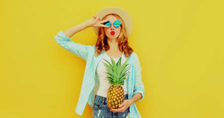 Summer portrait of beautiful woman with pineapple blowing red lips sending sweet air kiss wearing a straw hat, sunglasses over colorful yellow background Stok Fotoğraf - 152500326