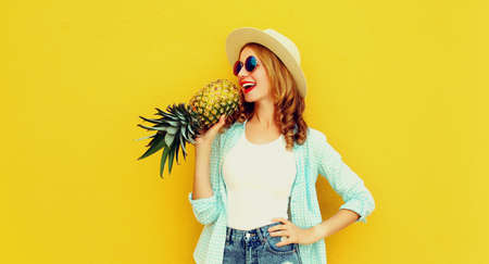 Summer portrait young woman singing with pineapple having fun wearing a straw hat, sunglasses over colorful yellow background Stok Fotoğraf - 152500336