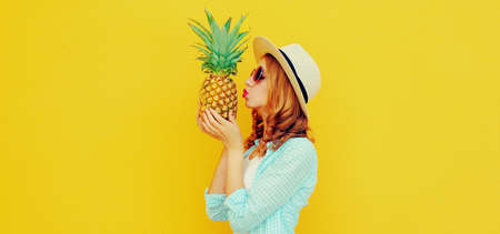 Summer image of attractive woman kissing tropical pineapple wearing a straw hat, sunglasses over colorful yellow background Stok Fotoğraf - 152500264
