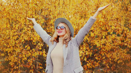 Autumn day, stylish young woman raising her hands up wearing gray coat, round hat over yellow leaves background Stok Fotoğraf - 153204691