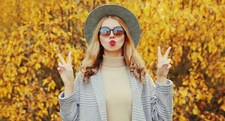 Autumn portrait of attractive woman blowing red lips sending sweet air kiss wearing gray coat, round hat on yellow leaves background Stok Fotoğraf - 153204695