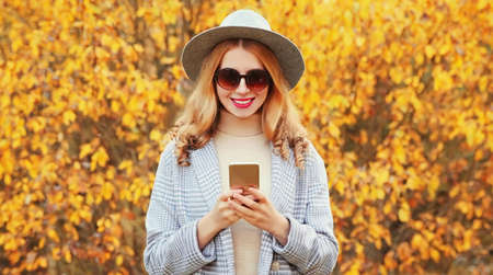 Autumn portrait of stylish young woman with smartphone wearing gray coat, round hat over yellow leaves background Stok Fotoğraf - 153204698