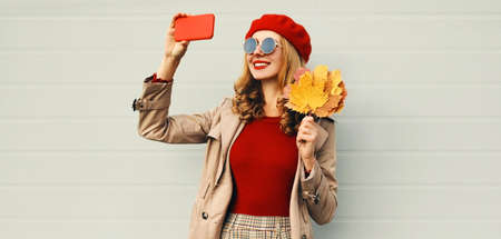 Autumn portrait of beautiful smiling woman taking selfie picture by phone with yellow maple leaves wearing red french beret over gray background Stok Fotoğraf - 153276114