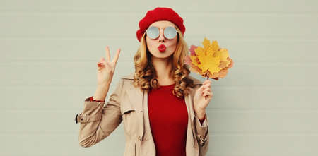 Autumn portrait of beautiful woman with yellow maple leaves, female model blowing red lips sending sweet air kiss wearing french beret over gray background Stok Fotoğraf - 153437003