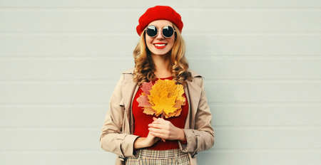 Autumn portrait of smiling young woman with yellow maple leaves wearing red french beret over gray background Stok Fotoğraf - 153276514