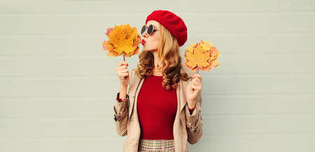Autumn portrait of beautiful woman with yellow maple leaves, female model blowing red lips sending sweet air kiss wearing french beret over gray background