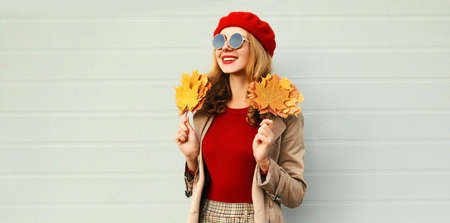 Autumn portrait of smiling young woman with yellow maple leaves wearing red french beret over gray background Stok Fotoğraf - 153276625