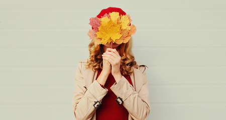 Autumn portrait of happy woman covering her eyes with yellow maple leaves over gray background Stok Fotoğraf - 153276298