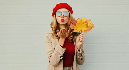 Autumn portrait of beautiful woman with yellow maple leaves, female model blowing red lips sending sweet air kiss wearing french beret over gray background Stok Fotoğraf - 153276707