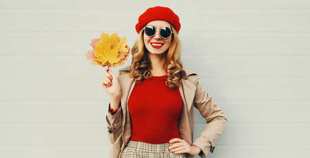 Autumn portrait of smiling young woman with yellow maple leaves wearing red french beret over gray background