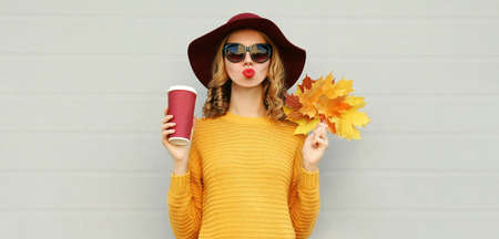 Autumn portrait of young woman with yellow maple leaves and cup of coffee wearing a sweater, hat over gray background Stok Fotoğraf - 153946680