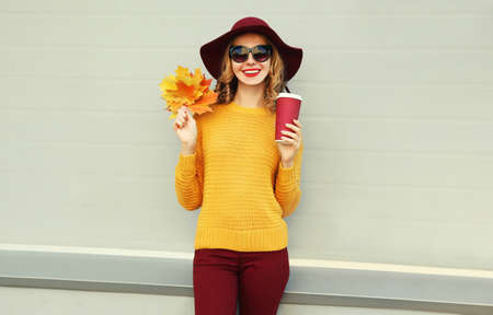 Autumn portrait of woman with yellow maple leaves and cup of coffee wearing a sweater, hat over gray background