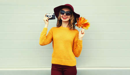Autumn portrait of smiling woman with retro camera and yellow maple leaves wearing sweater, hat over gray background Stok Fotoğraf - 154315687