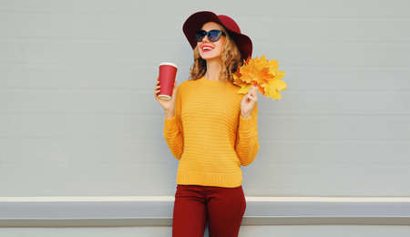 Autumn portrait of woman with yellow maple leaves and cup of coffee wearing a sweater, hat over gray background Stok Fotoğraf - 153946467