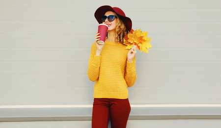 Autumn portrait of woman with yellow maple leaves and cup of coffee wearing a sweater, hat over gray background Stok Fotoğraf - 153946134