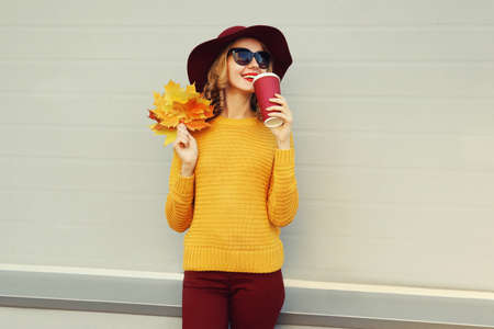 Autumn portrait of woman with yellow maple leaves and cup of coffee wearing a sweater, hat over gray background Stok Fotoğraf - 153946374