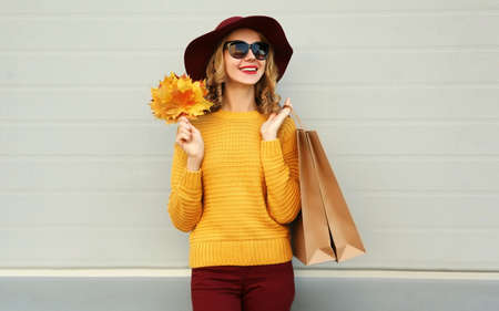 Autumn portrait of woman with shopping bags and yellow maple leaves wearing a sweater, hat over gray background Stok Fotoğraf - 155175746