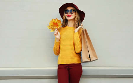 Autumn portrait of woman with shopping bags and yellow maple leaves wearing a sweater, hat over gray background Stok Fotoğraf - 155175747