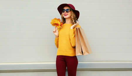 Autumn portrait of woman with shopping bags and yellow maple leaves wearing a sweater, hat over gray background Stok Fotoğraf - 155178751