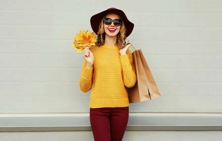 Autumn portrait of woman with shopping bags and yellow maple leaves wearing a sweater, hat over gray background Stok Fotoğraf - 155178754