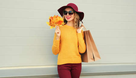 Autumn portrait of woman with shopping bags and yellow maple leaves wearing a sweater, hat over gray background