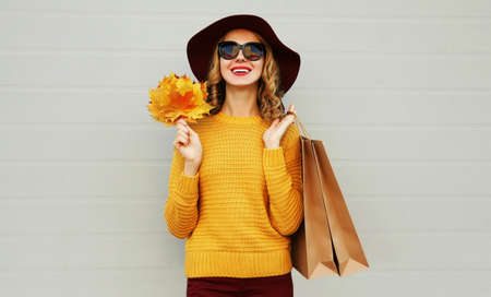 Autumn portrait of woman with shopping bags and yellow maple leaves wearing a sweater, hat over gray background Stok Fotoğraf - 155178753