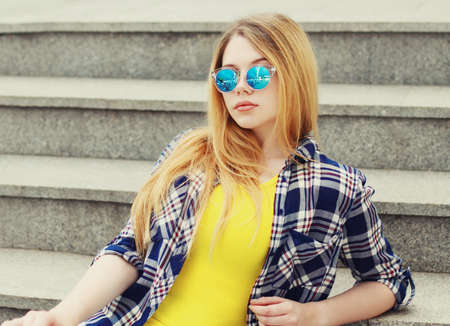 Close up portrait of blonde teenager girl wearing sunglasses looking at camera