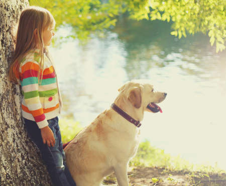 Little girl child with her Labrador retriever dog looking away in a park near river